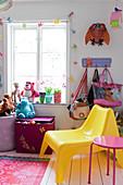 Gelber Kunststoff-Stuhl, Taschen und Stofftiere am Fenster im Kinderzimmer