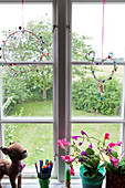 Window decoration with beads, indoor flowers, a pencil holder and a plush Bambi on a windowsill