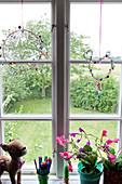 Fensterdekoration mit Perlen, Zimmerblumen, Stiftehalter und Plüsch-Bambi auf Fensterbank