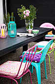 Colourful chairs with cushions around a black wooden table with lanterns and a bouquet of roses