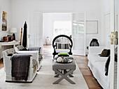 Weiße Hussenmöbel, gepolsterte Hocker als Couchtisch und Rattanstuhl im Wohnzimmer
