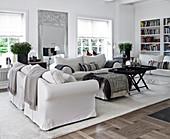 Weiße Hussenmöbel, Ottoman und Couchtisch im Wohnzimmer
