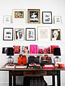 Regale mit Fotos, Kunstwerken und Büchern über altem Schreibtisch aus Holz