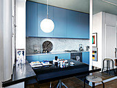 Black dining table in a modern open kitchen with blue fronts