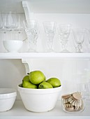 Green pears in a bowl on the kitchen shelf with glasses