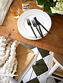 Black cutlery, a stack of plates, and apple juice on the wooden table