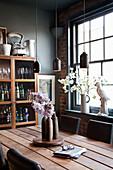 Holztisch mit Lederstühlen, darüber Pendelleuchten vor Geschirrschrank und Fenster