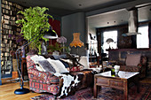 Cushions and animal fur on a sofa with ethnic cover, behind a console table with a houseplant in the living room