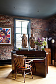 Piano with Asian statues in the room, framed poster with Queen Elizabeth on a brick wall