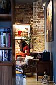 Blick auf Sessel mit Ethno-Bezug vor Backsteinwand in Zimmerecke