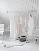 Clothes rail under the eaves of a sloping ceiling in a white bedroom