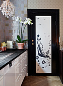 White kitchenette with black worktop, orchid, and chandelier, door with an Asian motif