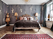 Double bed with antique bed head flanked by floor lamps and gold coloured statue in bedroom