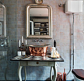 Metal sink on a wooden table under an antique mirror in the bathroom