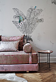 An elegant sofa and a side table in front of a wall papered with palm tree wallpaper