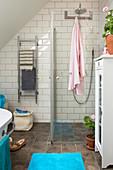 Duschbereich mit Glasabtrennung im Badezimmer mit weißen U-Bahn-Fliesen