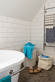 Laundry basket, magazine basket, and towel dryer in a bathroom with white subway tiles, bathtub in foreground