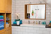 Waschbecken mit Ablage, darüber Wandspiegel und Holzschrank mit Regal im Badezimmer mit weißen U-Bahn-Fliesen im Dachgeschoss