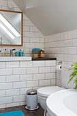 Washbasin with shelf, above wall mirror and wooden cabinet with shelf in the bathroomn