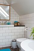 Toilette im Badezimmer mit weißen U-Bahn-Fliesen im Dachgeschoss