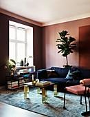 Elegantes Wohnzimmer mit Wänden in Altrosa und blauem Sofa