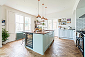 Herringbone parquet floor and island counter in open-plan kitchen in country-house style