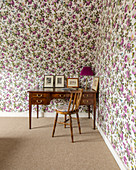 Old chair and antique desk against floral wallpaper