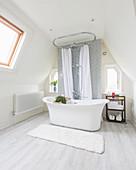Free-standing bathtub in elegant attic bathroom with sloping walls