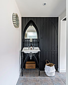 Antique sink and washstand against black wooden wall in converted barn