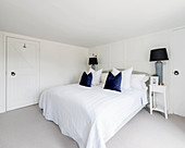 Double bed in white bedroom