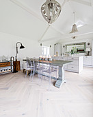 Hefty dining table and classic chairs in front of kitchen area in converted barn