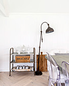 Vintage serving trolley and standard lamp in dining area