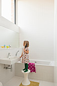 Little girl standing on stool at sink