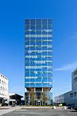 Kubisches Hochhaus mit Glasfassade vor blauem Himmel