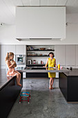 Mother and daughter in cutting-edge kitchen in shades of grey