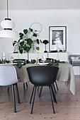 Gedeckter Weihnachtstisch mit grauer Tischdecke, dahinter Sideboard mit Zimmerpflanze