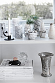 Marble vases on shelf below window and above stacked magazines and silver goblet