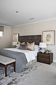 Gilt-framed pictures of fingerprints flanking bed in bedroom