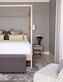 Modern, wooden, four-poster bed in bedroom in shades of grey