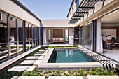 Pool in courtyard of modern house with open walls
