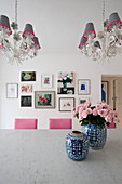 Roses in Chinese vases on table below chandeliers with lampshades