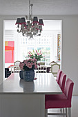 Hot-pink bar stools at kitchen counter, roses in Chinese vase and chandeliers with lampshades