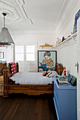 Antique wooden bed next to blue chest of drawers and large portrait of boy on wall