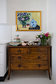 Crockery and vase of flowers on rustic chest of drawers below painting