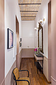 Console table and gilt-framed mirror in narrow, two-tone hallway