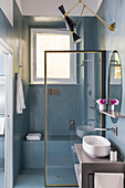 Masonry bench in shower behind glass screen in bathroom with grey-blue walls