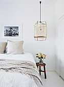 Double bed with light-colored bed linen, stool as a bedside table with a bouquet of roses, hanging lamp above