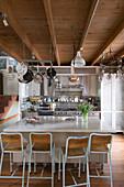 Barhocker an der Kücheninsel in der offenen Küche mit Balkendecke