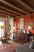Alte Kommode vor rostroter Wand im rustikalen Wohnzimmer