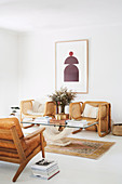 Leather armchairs and rattan armchairs around coffee table with glass top